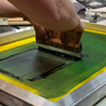 adult pulling squeegee using screenprinting technique