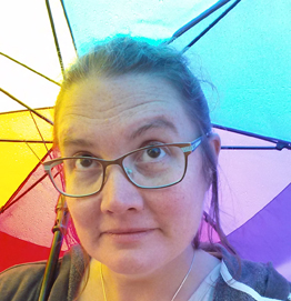 photo of founder and director April Hoff under a rainbow umbrella