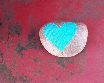 photo of uncoated gray love-rock with aqua colored heart decoupage sitting on a red metal background with rust