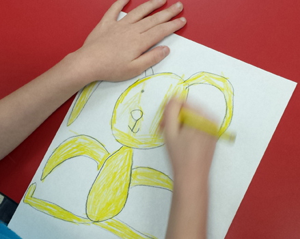 photo: overhead view of child's hands drawing a yellow rabbit on white paper against a red table