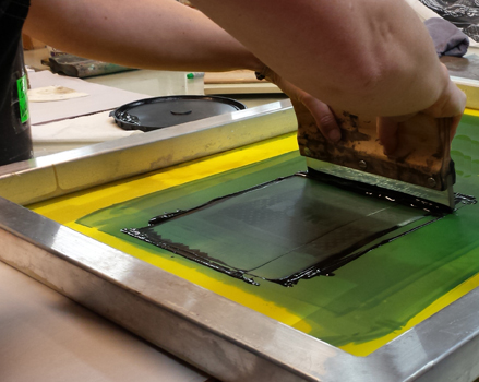 photographic image of an adult pulling an inked squeegee through a screenprinting frame