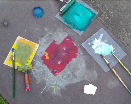 photographic image of paintbrushes, brayers, paper, and individual paint palettes of yellow, blue, white, and teal against concrete